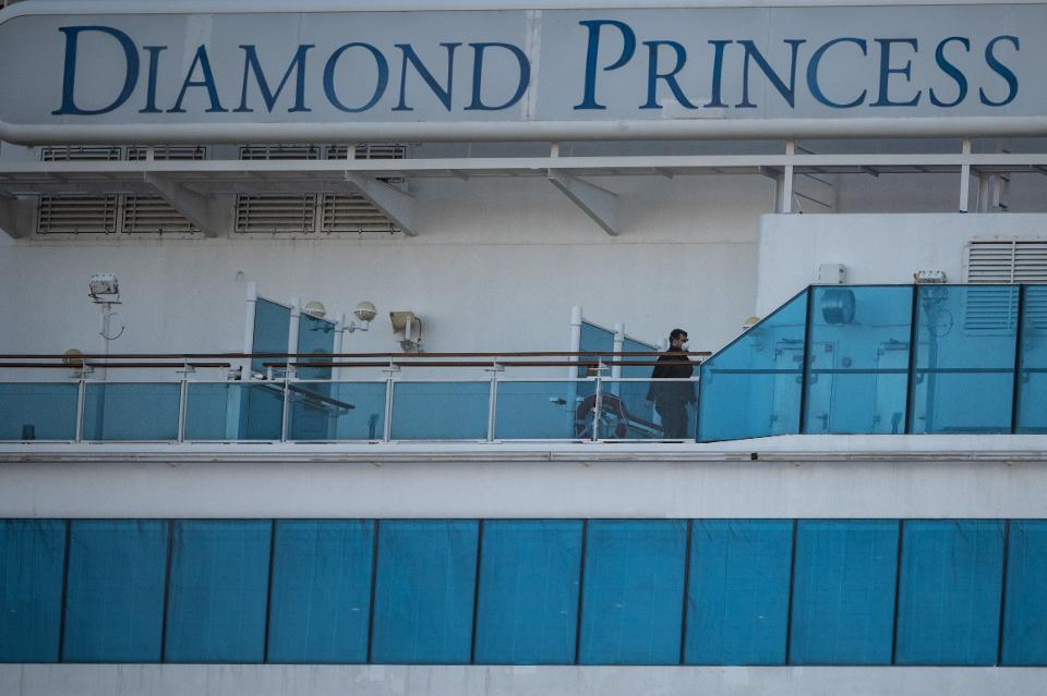 A crew member wearing a face mask walks on the deck of the Diamond Princess cruise ship at Daikoku pier cruise terminal in Yokohama on February 24, 2020.