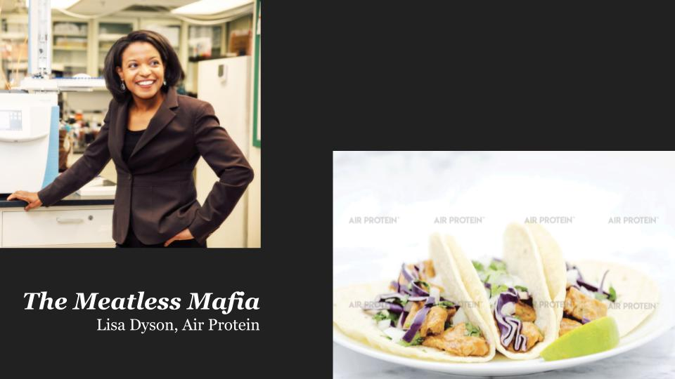 A Black woman in a brown suite smiling to the right and a seperate plate of tacos.