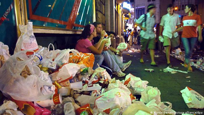 A pile of bafs and cartons from fast food restaruants litter the street