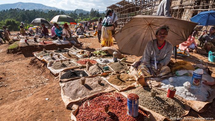 A man sits under an umbrella at a market selling beans