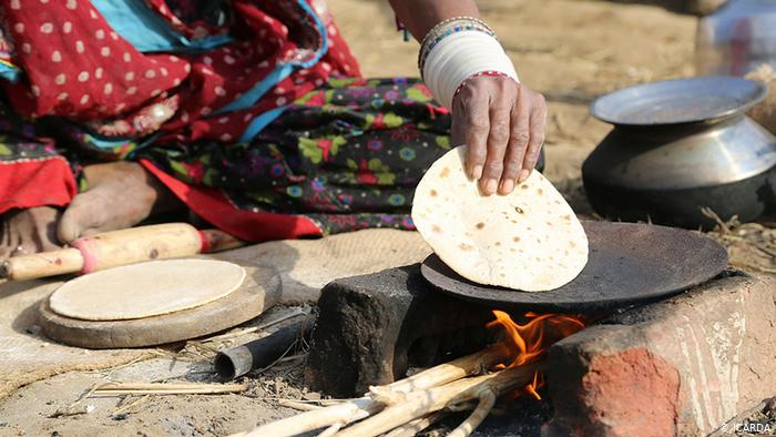 A woman cooks on a simple outdoor stove