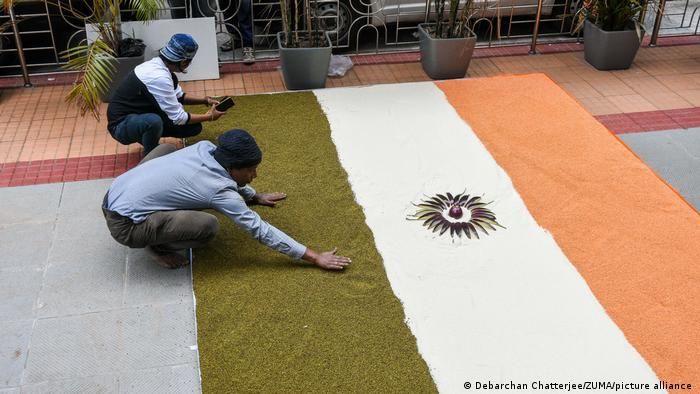 Two men create an Indian flag on the ground using rice and lentils