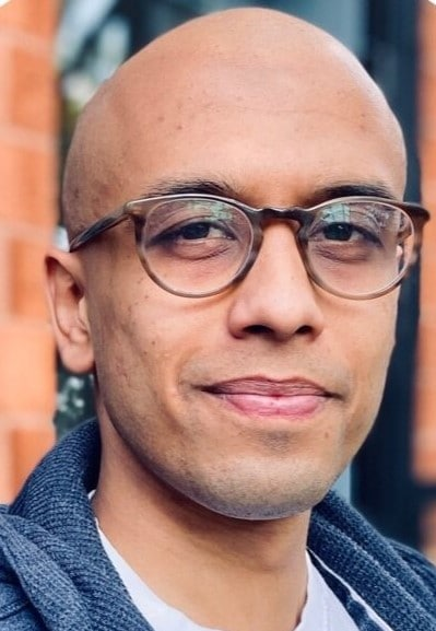 a bald man with brown skin and glasses looking into camera